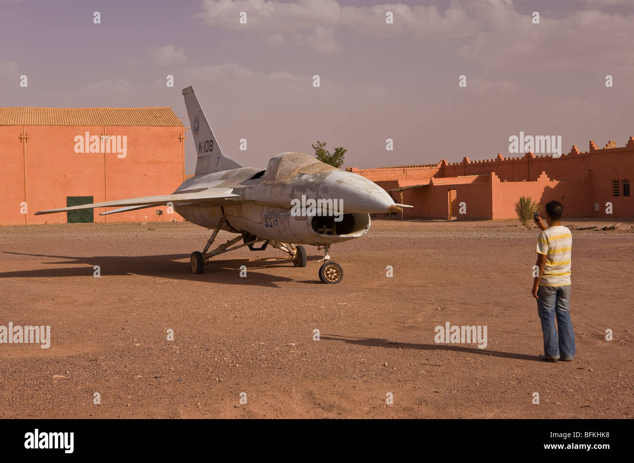 OUARZAZATE, MOROCCO - Tourist takes photo of jet fighter prop on movie set at Atlas Corporation Studios. - Stock Image