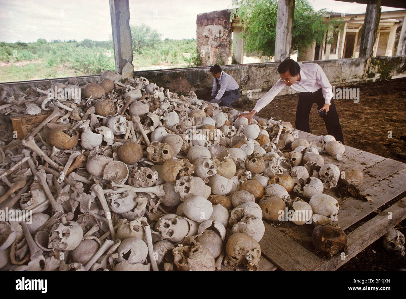 Haing Ngor, with a pile of skulls and bones of executed victims of the Pol Pot regime, - Stock Image