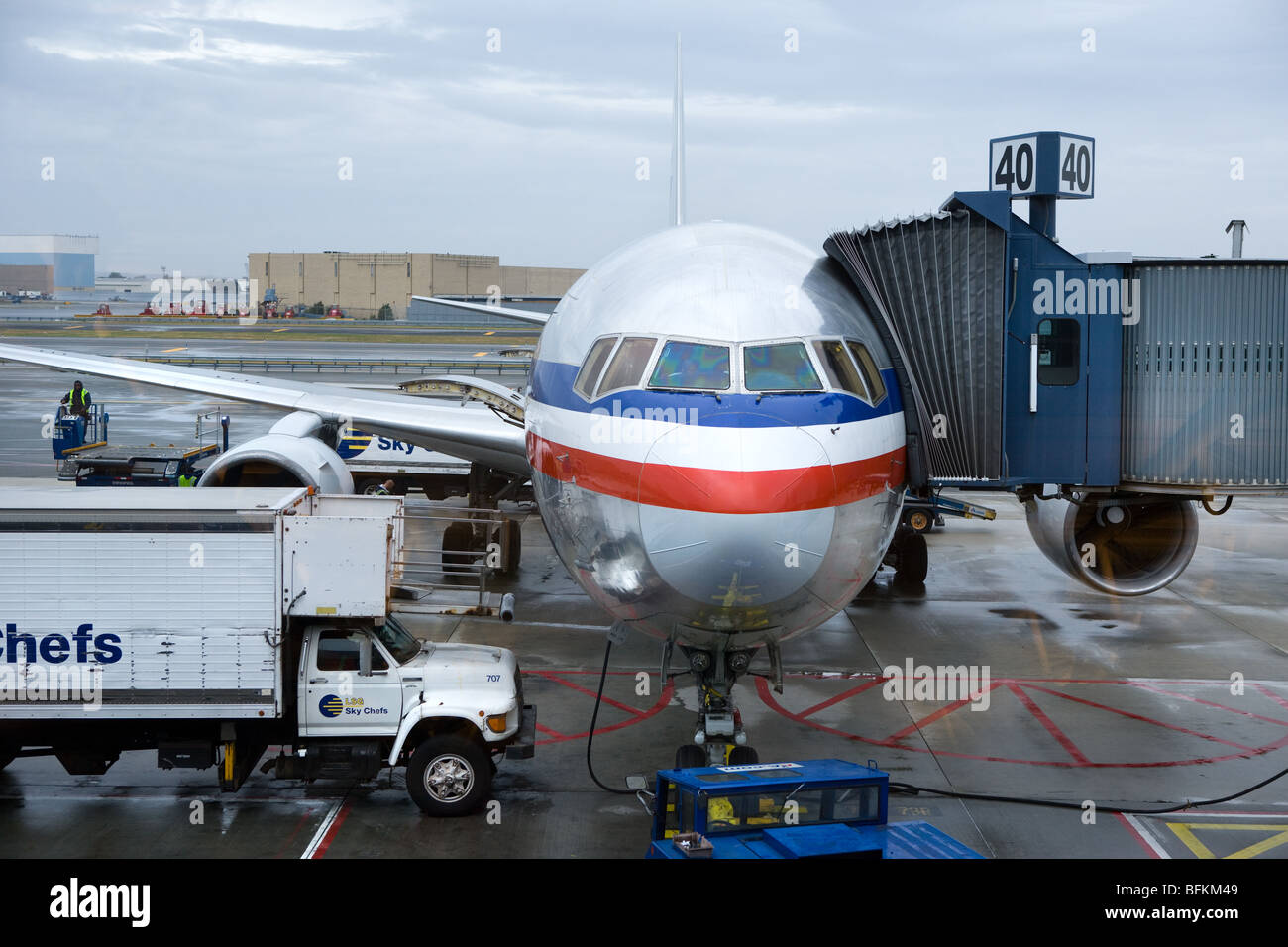Passengers board a US Airways jet en route from JFK in New York to Mexico on the walkway as food trucks bring food. - Stock Image