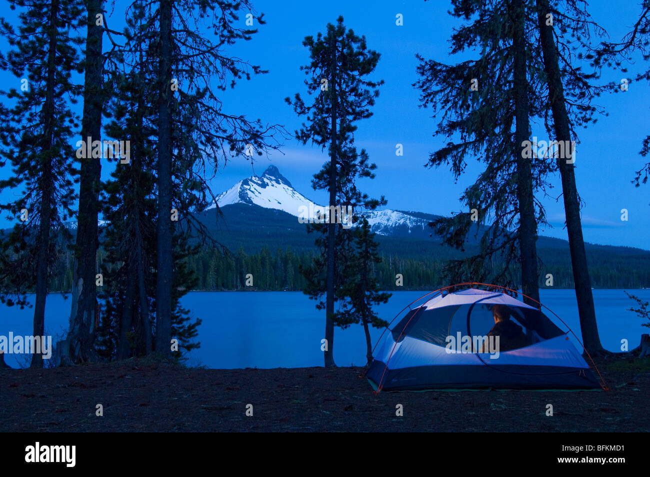Camping at Big Lake with dusk view of Mount Washington; Cascade Mountains, Oregon. - Stock Image