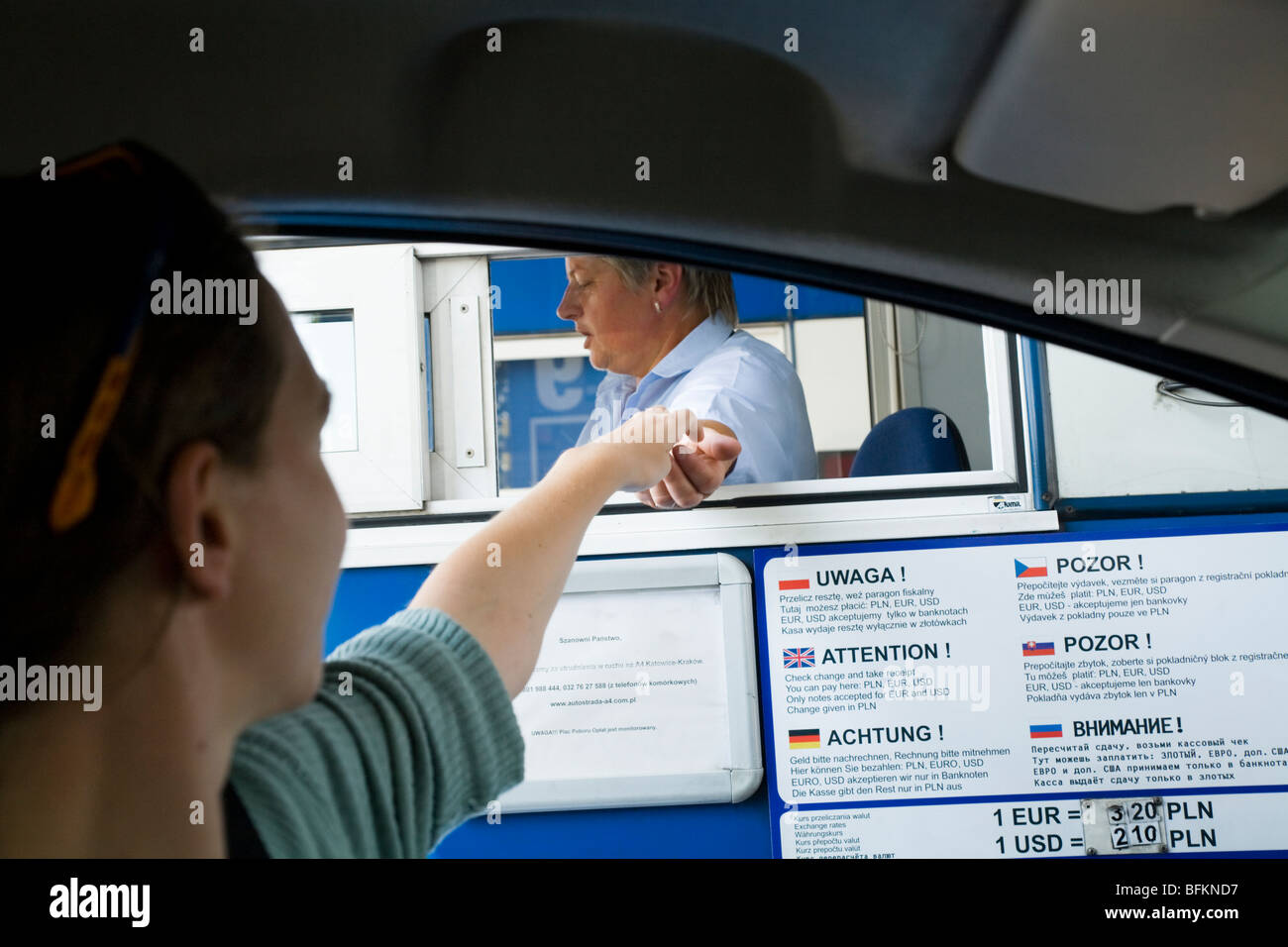 Tourist driver pays a road toll at a Polish motorway toll booth. Near Krakow, Poland. - Stock Image