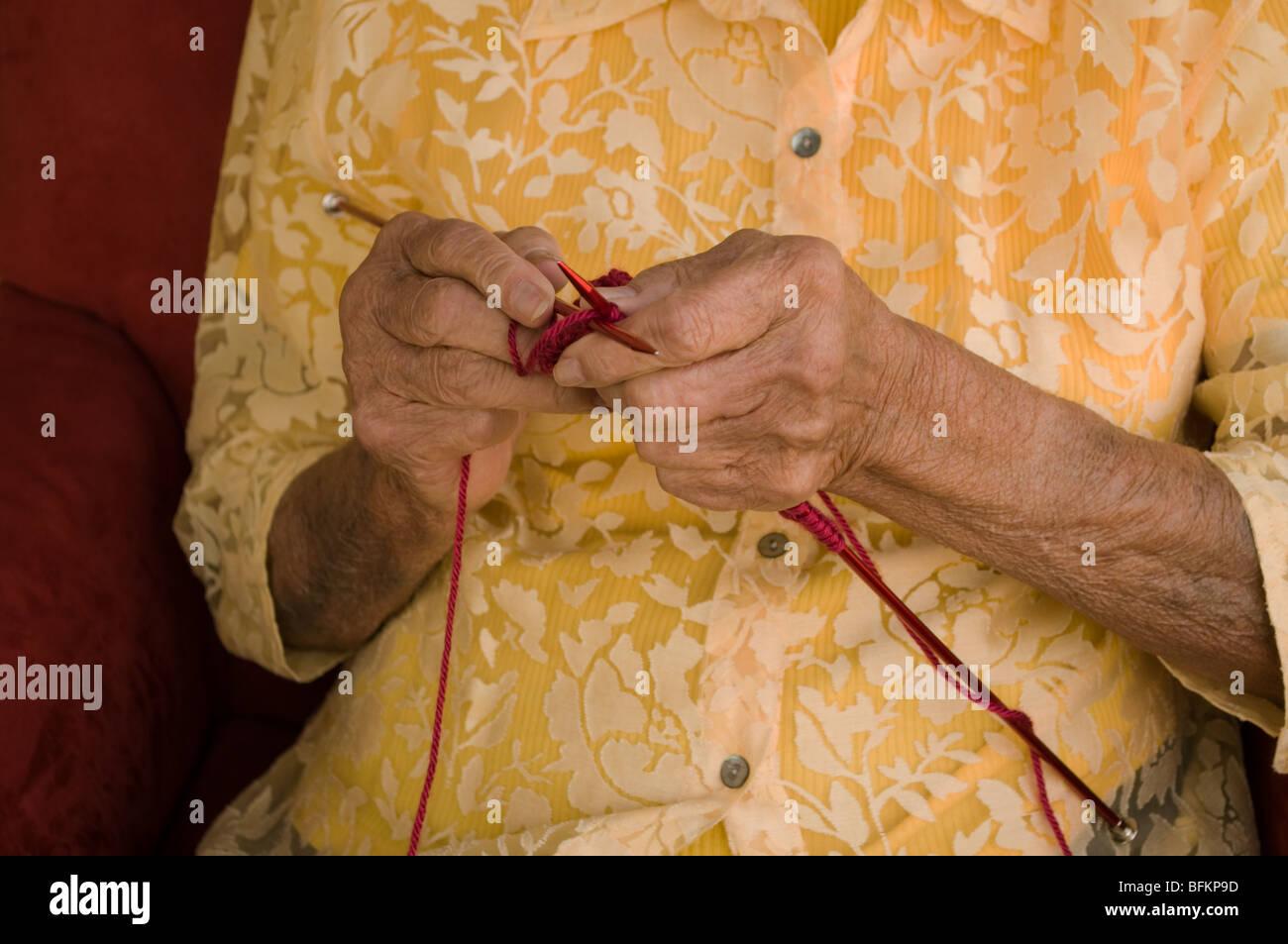 elderly caucasian woman knitting with burgandy wool yarn - Stock Image