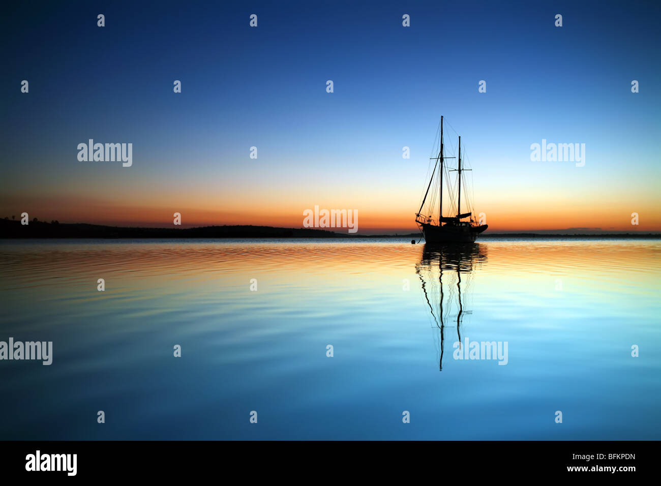 BHZ A silhouetted yacht lies at anchor in the bay at Saint Helen's Tasmania Australia - Stock Image