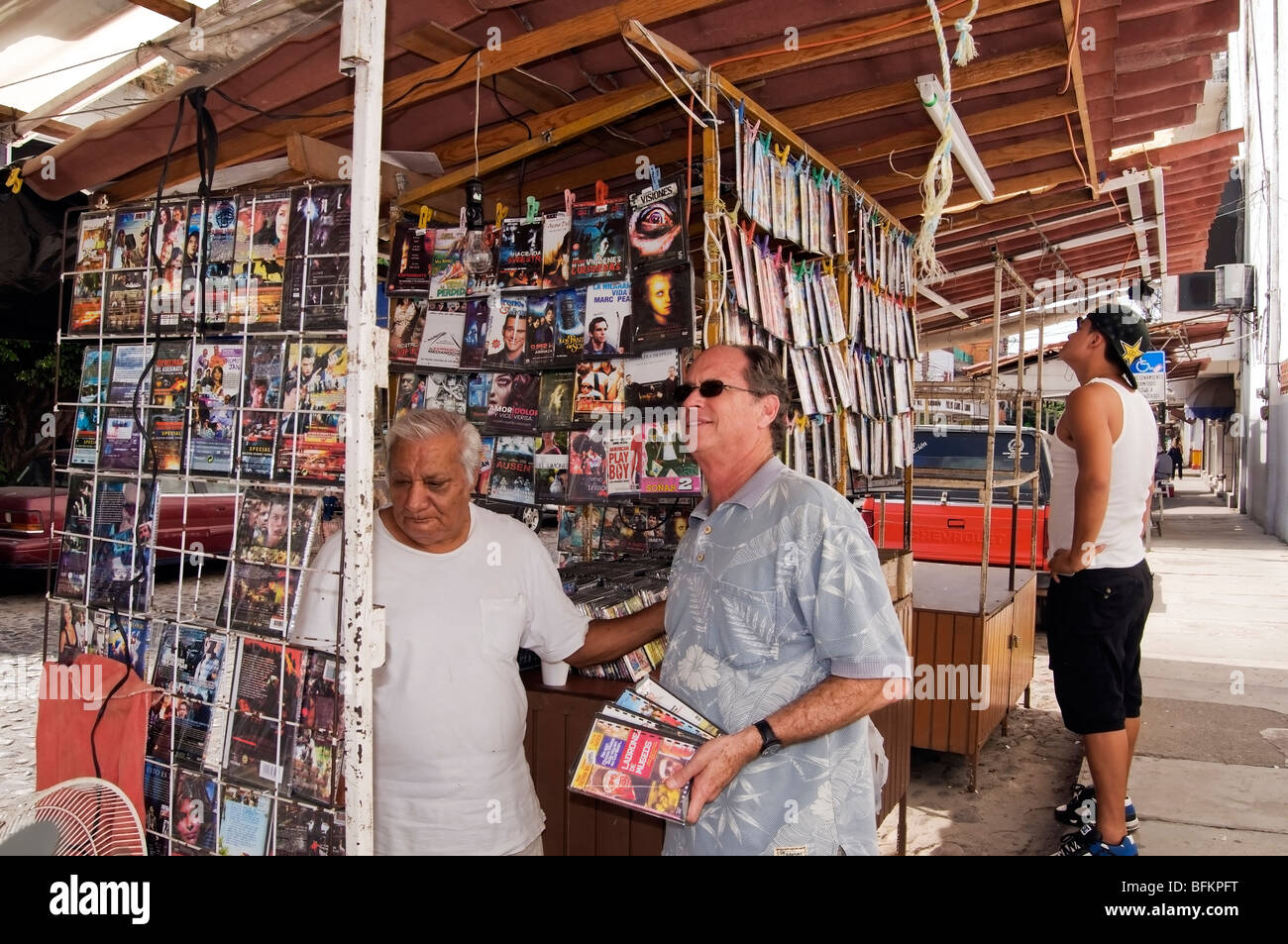 A street vendor selling pirated DVD movies shows a variety