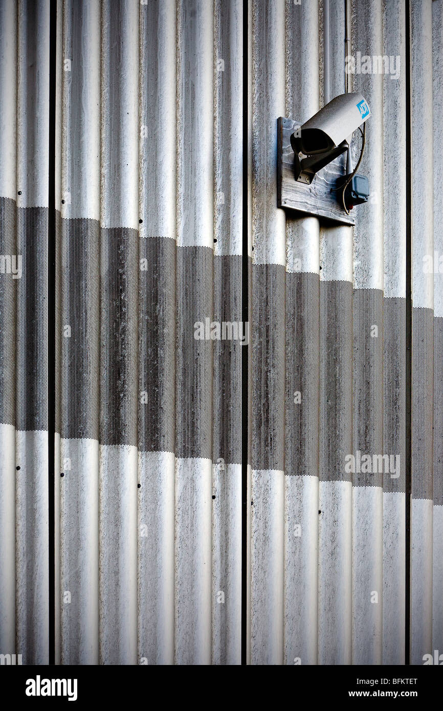 Security camera sitting on corrugated and galvanized steel panels at the side of The Lowry at Salford Quays, Manchester - Stock Image