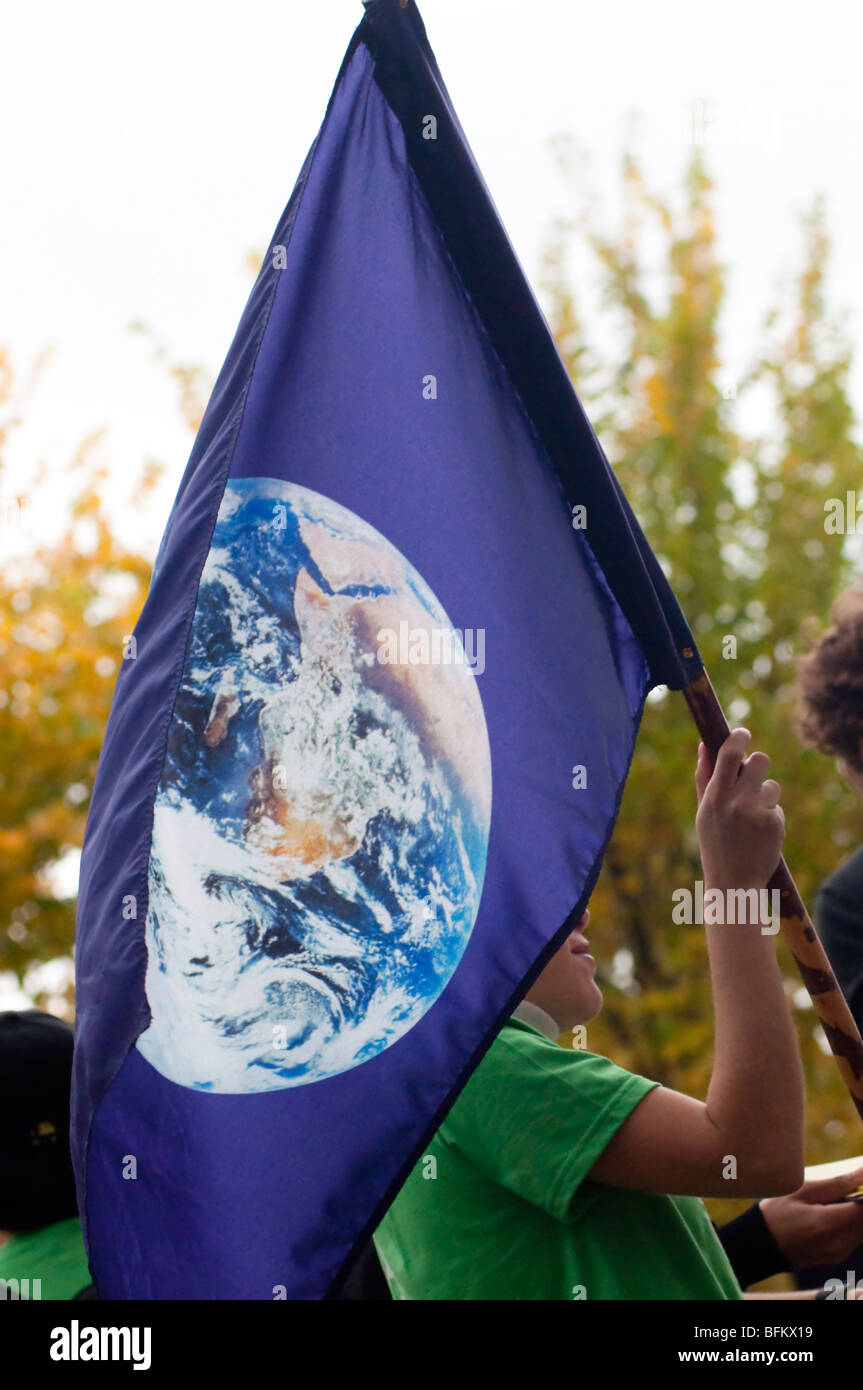 A blue flag with an image of plant earth flies over an environmental protest event. - Stock Image