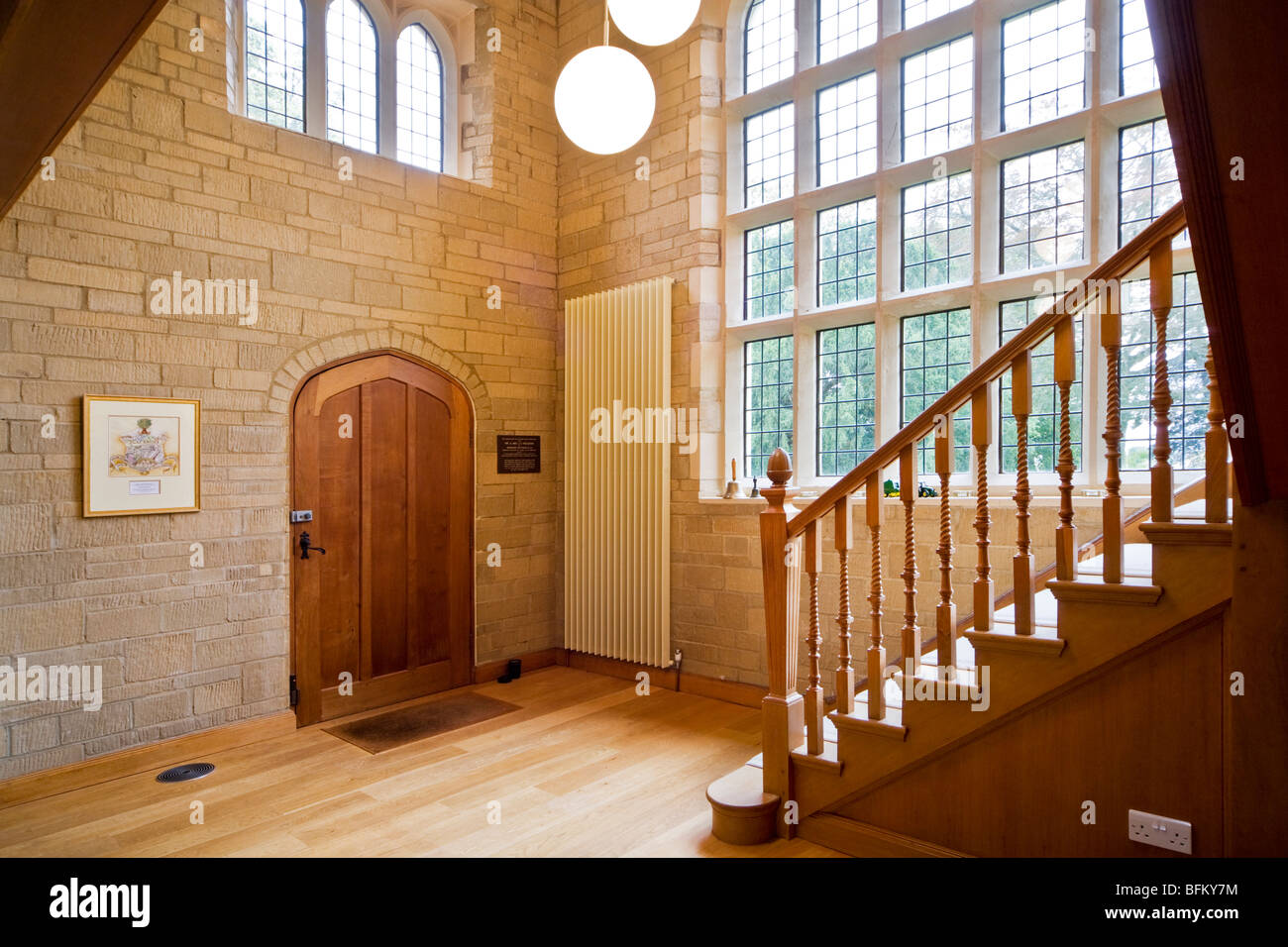 Wooden entrance door and staircase and stone hallway with mullioned windows in a grand modern contemporary English - Stock Image