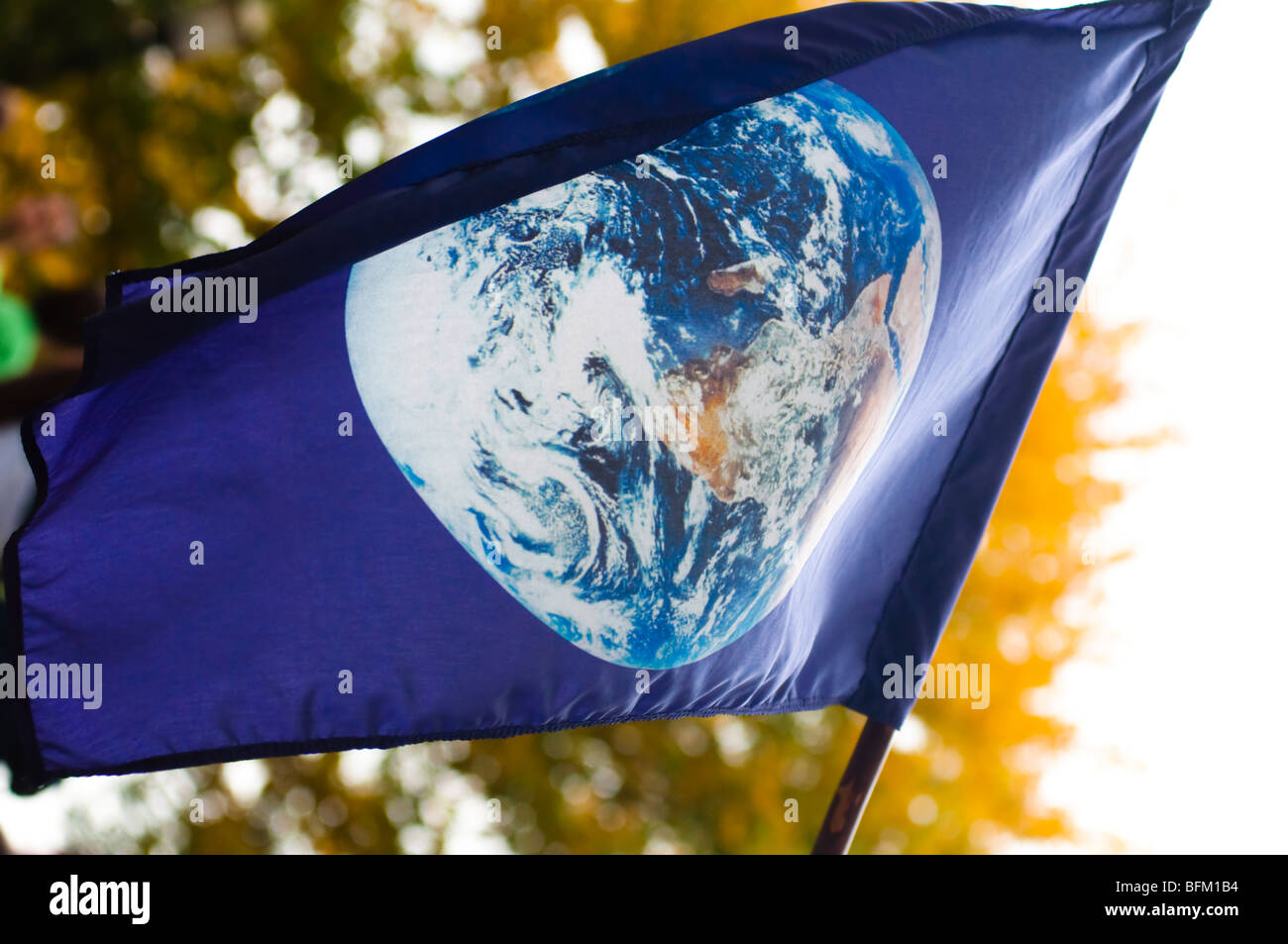 A blue flag with an image of plant earth flies over an environmental protest event. Stock Photo