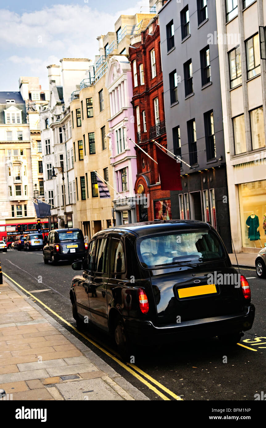 London street with taxicab and shops on sunny day - Stock Image