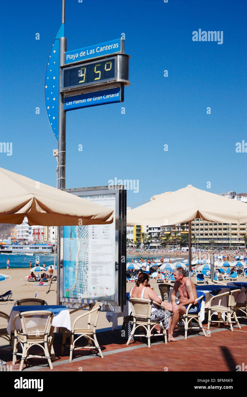 Couple at outdoor cafe overlooking Playa de Las Canteras in Las Palmas on Gran Canaria. Temperature guage showing - Stock Image
