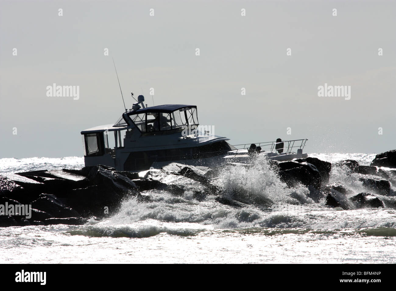 Boat running aground on rocks - Stock Image