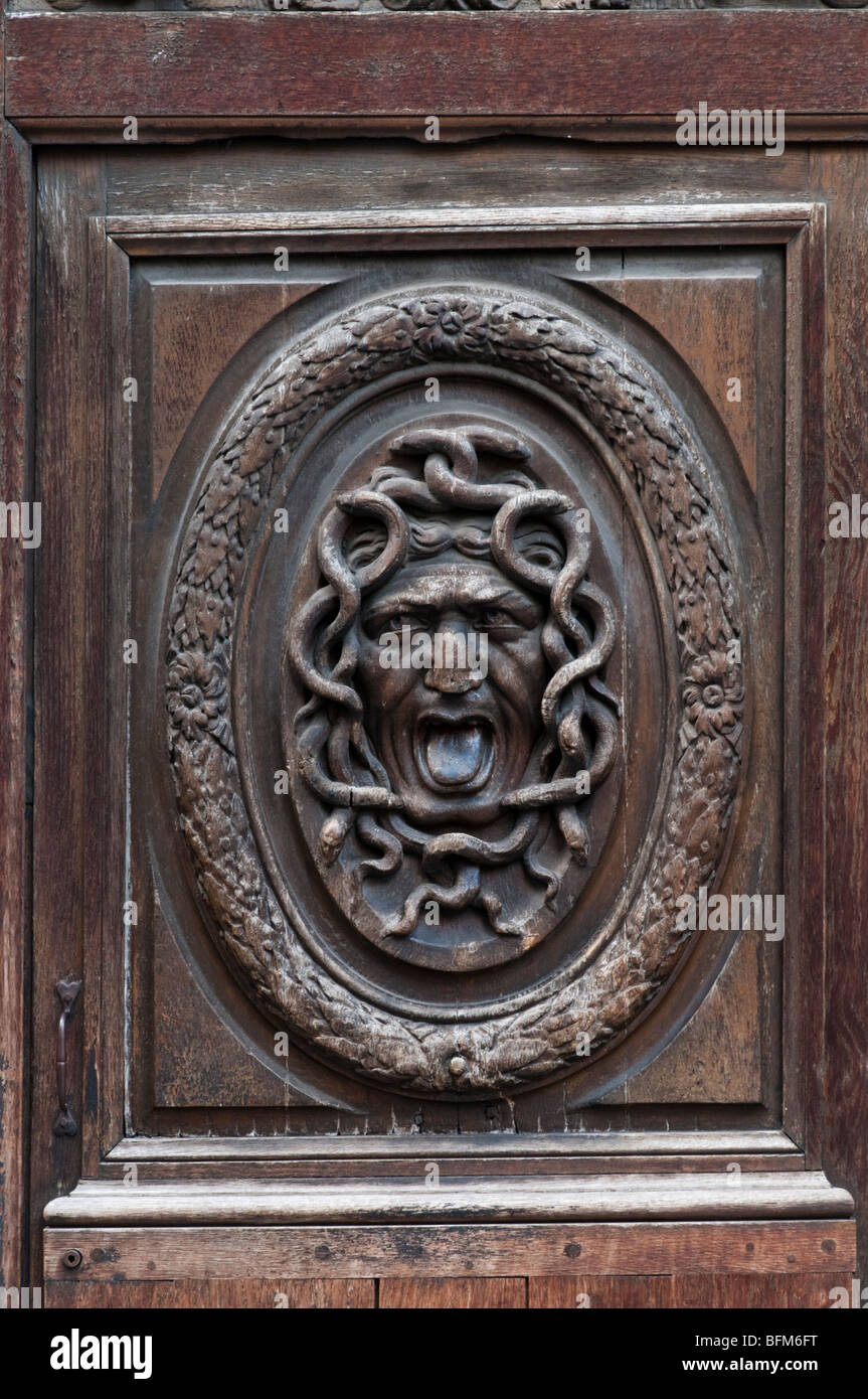 Detail of a scary face carved into a big old wood door in Le Marais district, Paris - Stock Image