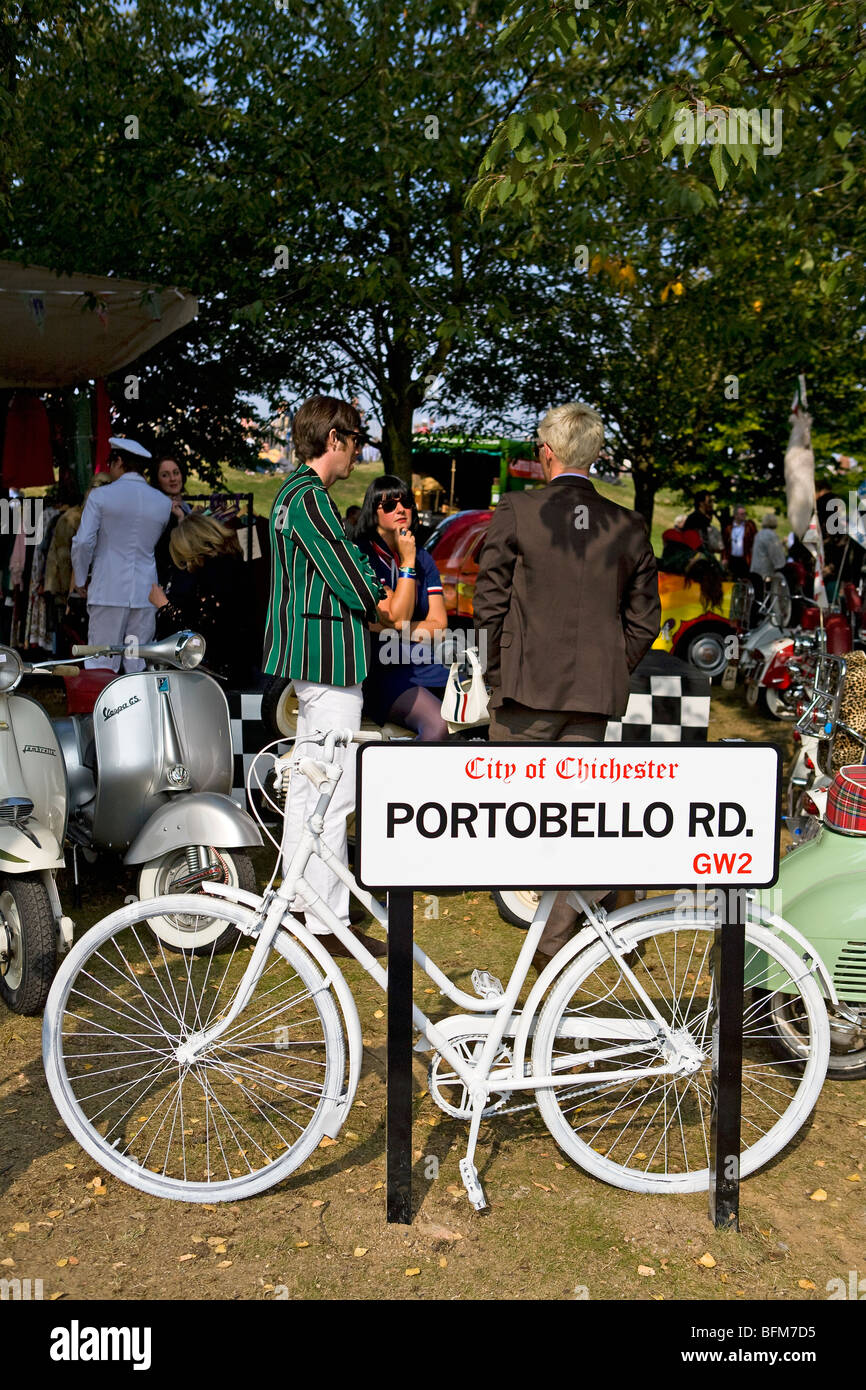 White bicycle resting against Portobello Road street sign at Goodwood Revival, Chichester, West Sussex, England - Stock Image