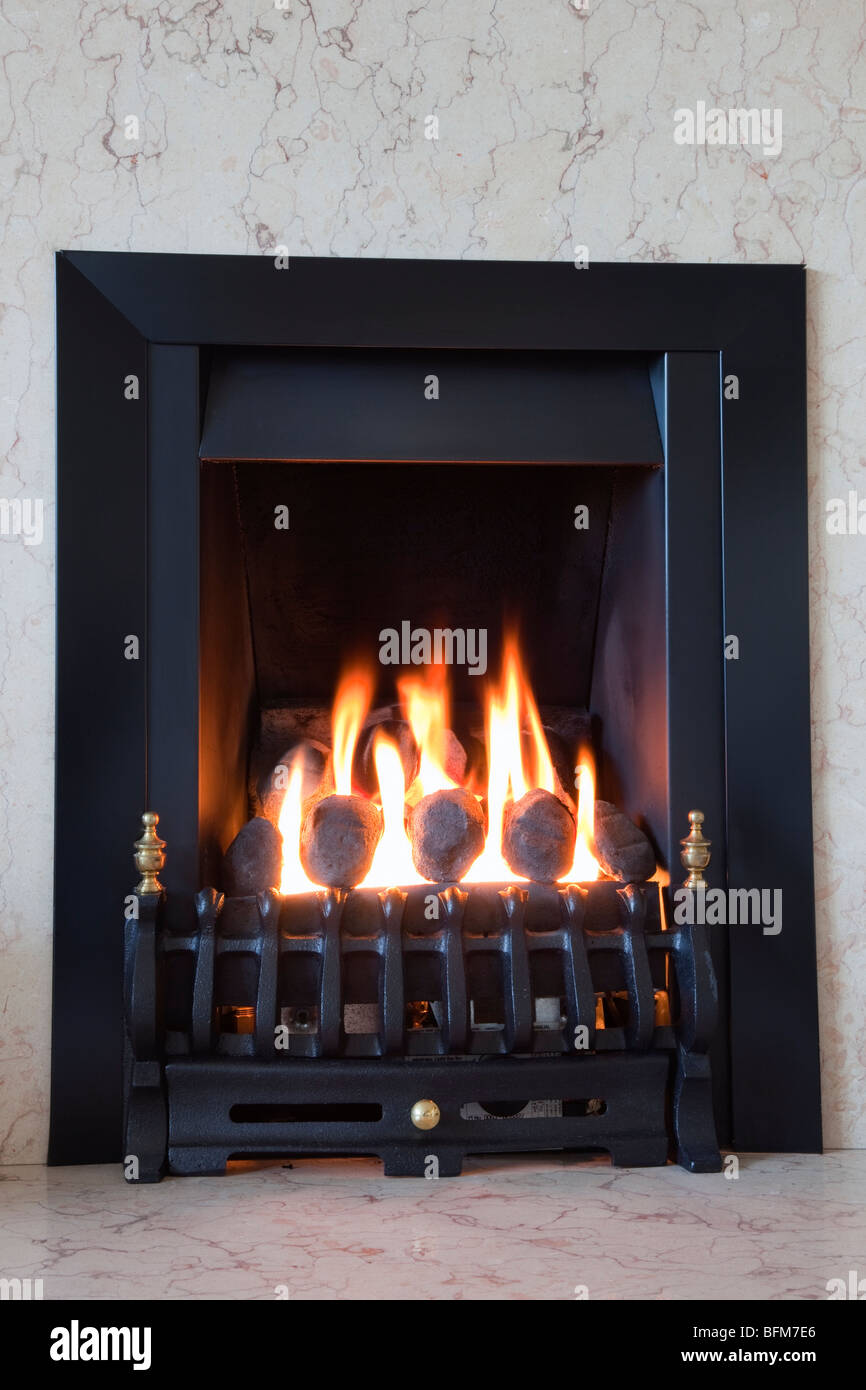 Propane gas fire with artificial coals burning in a cosy domestic fireplace. England, UK,  Britain - Stock Image