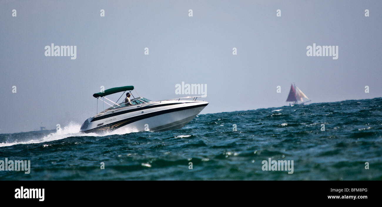 A motor-boat in foreground, and  a sailboat in background. Slantwise cropped. - Stock Image