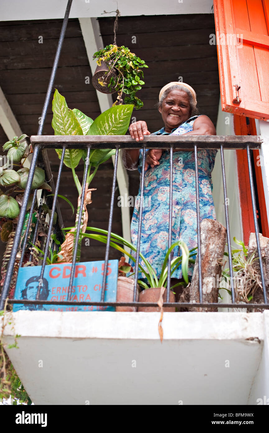 Cuban woman smiles down from balcony - Stock Image