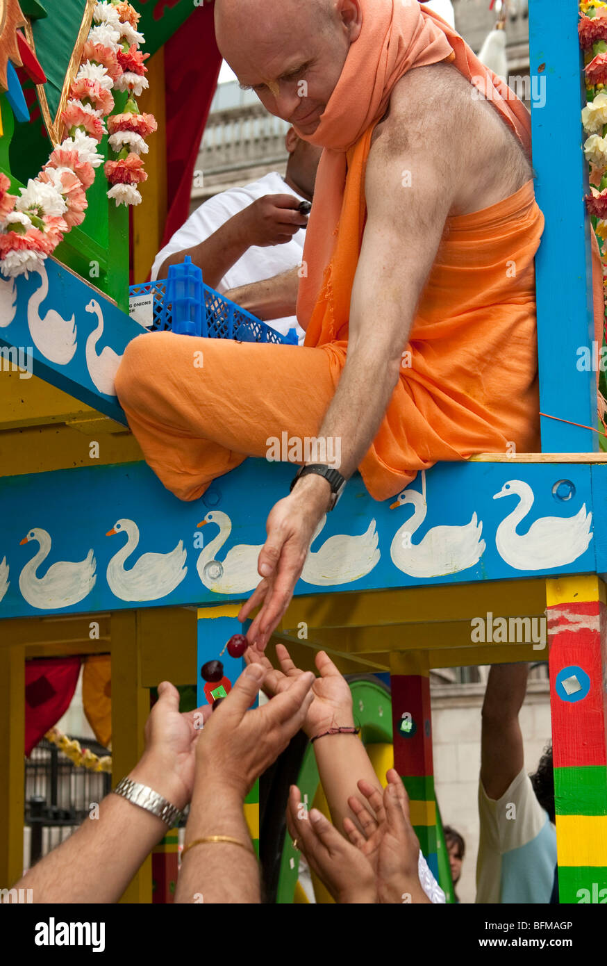 Hare Krishna distributing fruits to worshippers at the Ratha Yatra  The Hindu festival of chariots in London UK Stock Photo