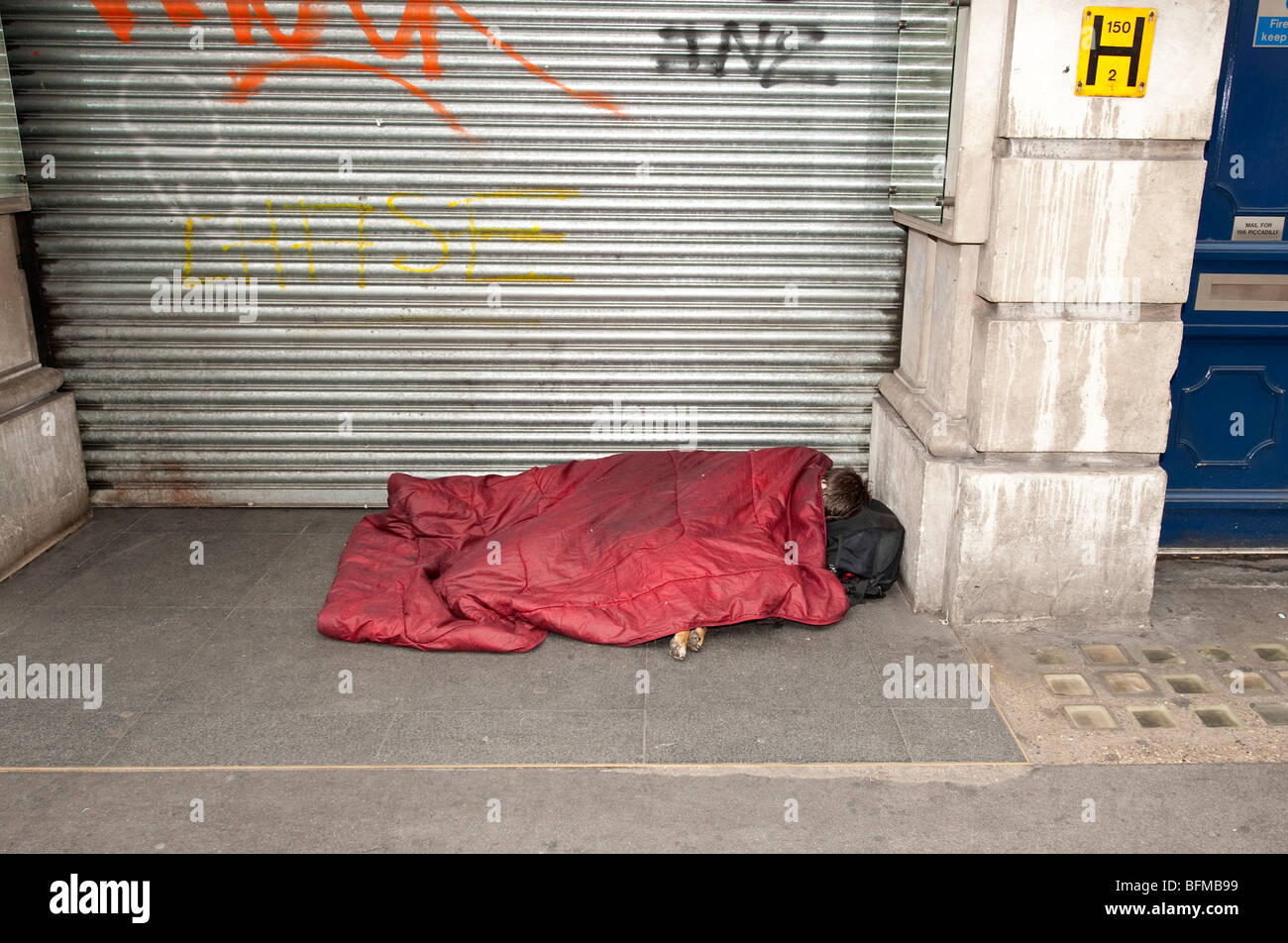 A person with dog  sleeping outside closed shop - Stock Image