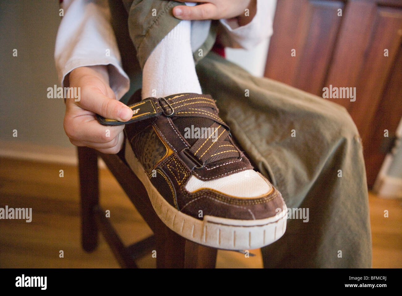 Close up of a child putting on his sneakers using a velcro strap, getting dressed - Stock Image