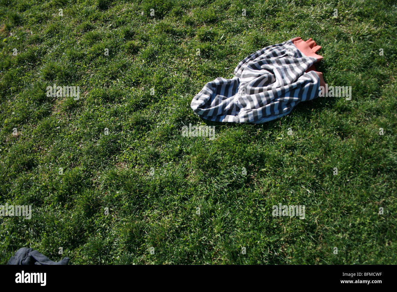 a jacket left laying in a grassy field - Stock Image
