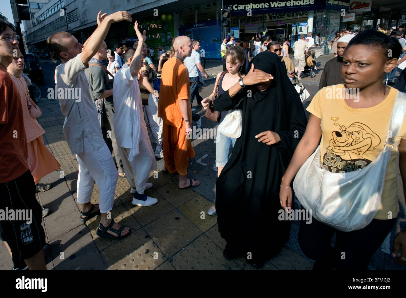 a group of hare krishna devotees walk past some muslims in oxford street london - Stock Image