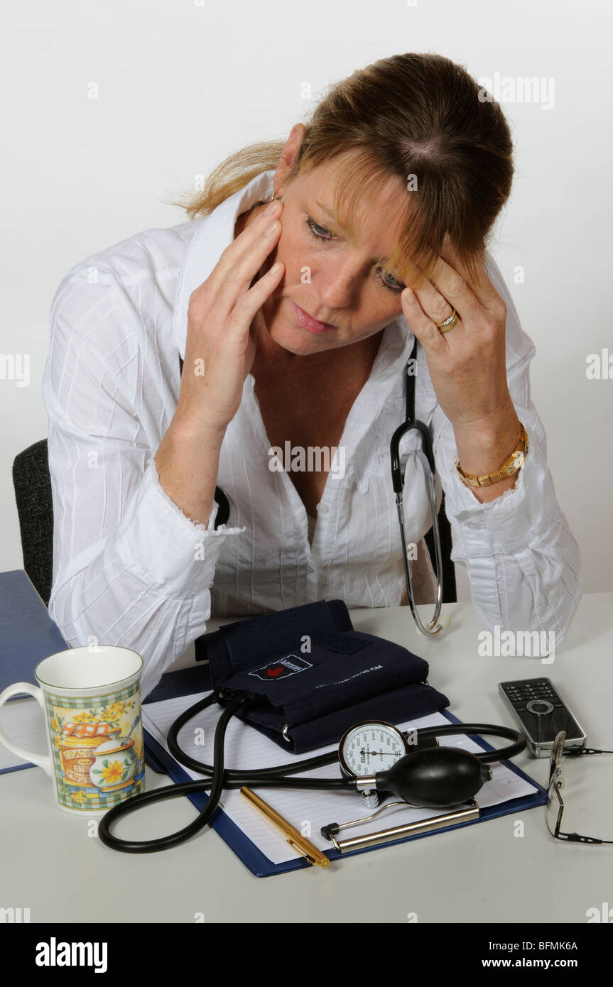 Stressed female medical practitioner sitting at desk with head in hands - Stock Image
