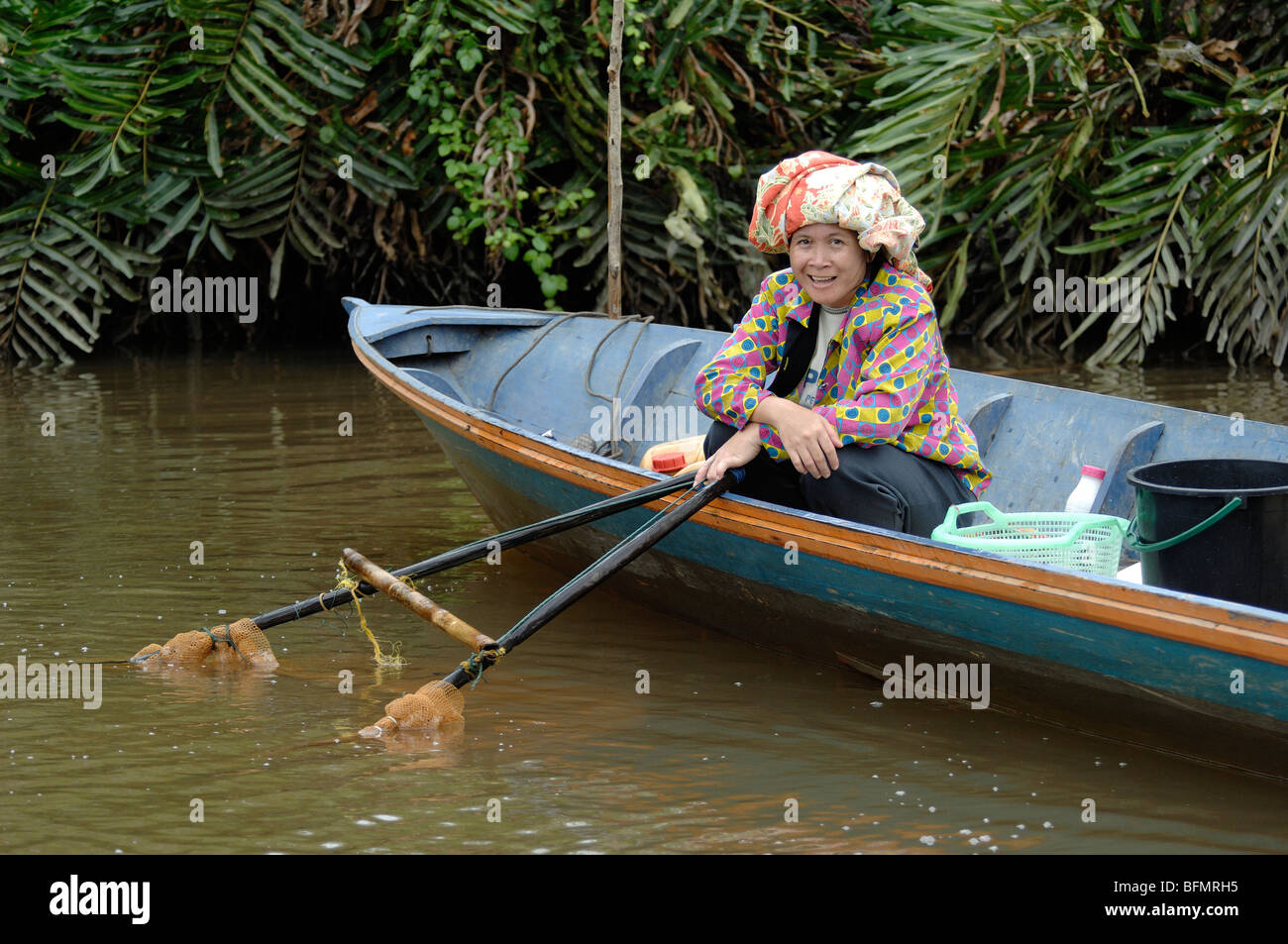 Smiling Sabah Fisher Woman Shrimp Fishing from Boat with Net in Klias Mangrove Wetlands, Sabah, Malaysia, Borneo - Stock Image