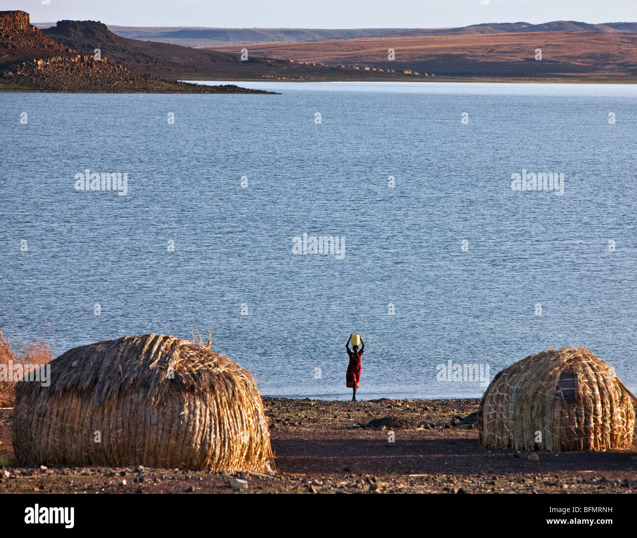 An El Molo woman fetches water from Lake Turkana. Typical dome-shaped El Molo houses in the foreground are made - Stock Image