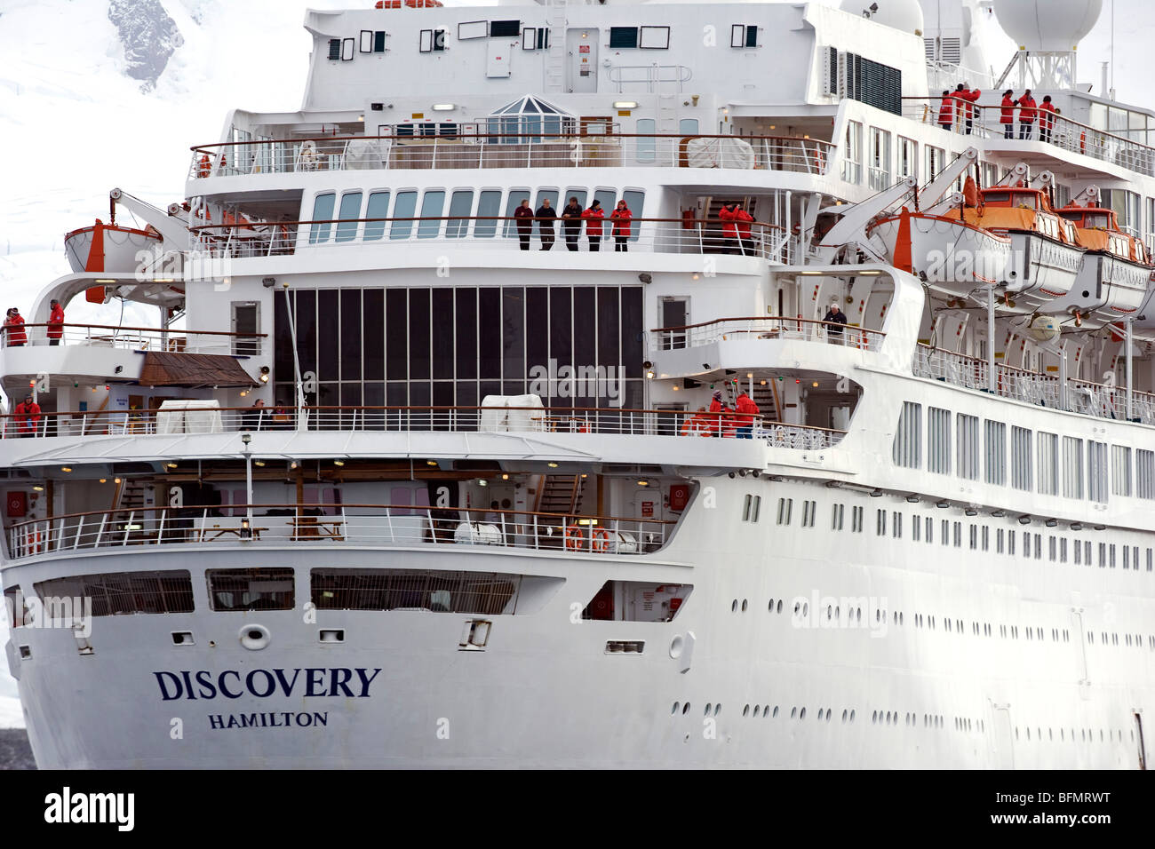 Antarctica, Antarctic Sound. The stern of the cruise ship Discovery, passengers clad in the distinctive red 'Polar - Stock Image