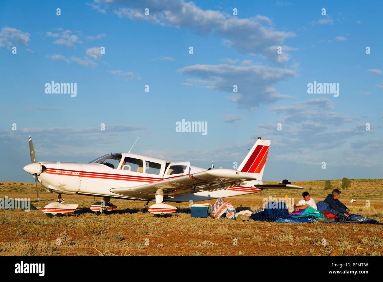 Australia, Queensland, Birdsville.  Men camp next to their plane on a bush airstrip during the annual Birdsville - Stock Image
