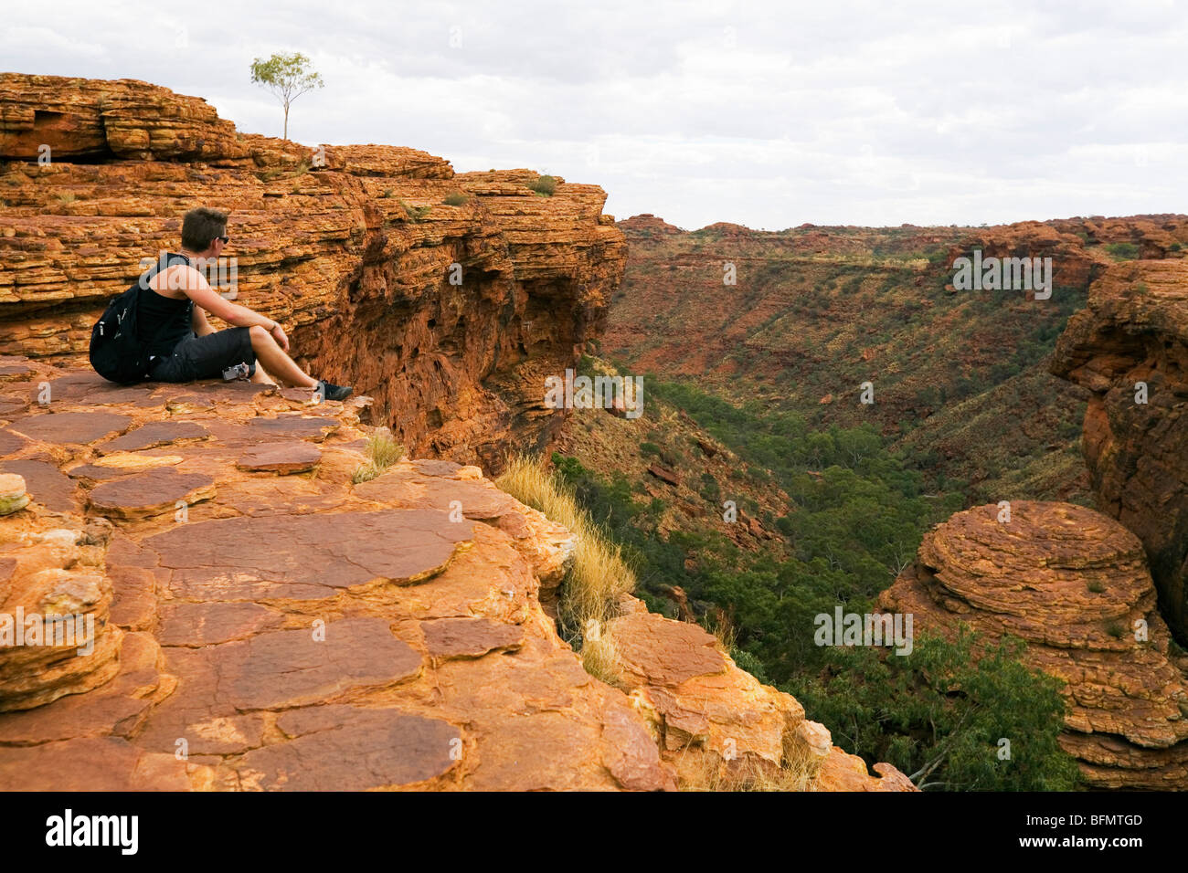 Australia, Northern Territory, Watarrka (Kings Canyon) National Park.  A hiker looks out over Kings Canyon. (MR) Stock Photo