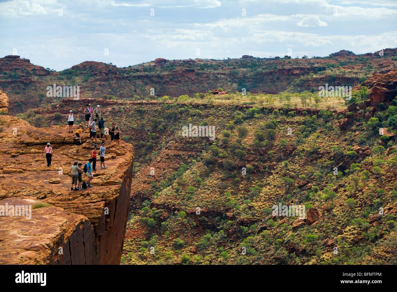 Australia, Northern Territory, Watarrka (Kings Canyon) National Park. Hikers on the canyon's edge. (PR) - Stock Image