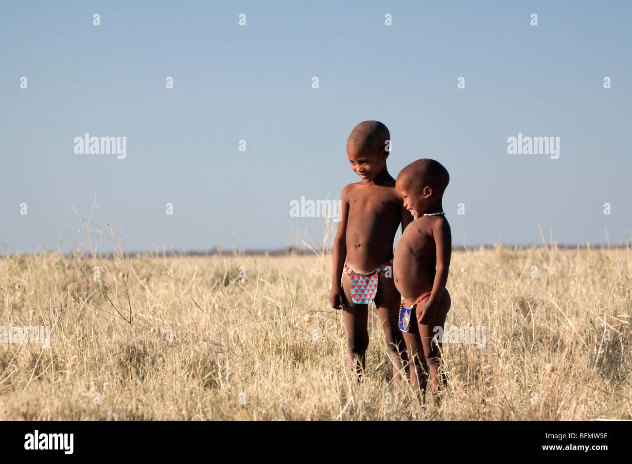 Botswana, Makgadikgadi. Bushmen children standing in the dry grasses of the Kalahari - Stock Image