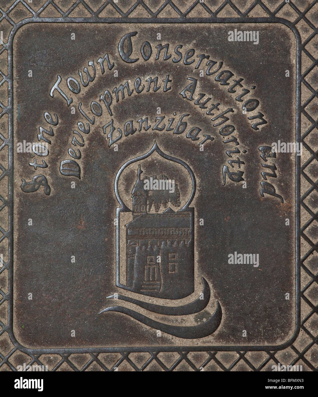 Tanzania, Zanzibar, Stone Town. A manhole cover in Stone Town highlighting the important contribution made by the - Stock Image