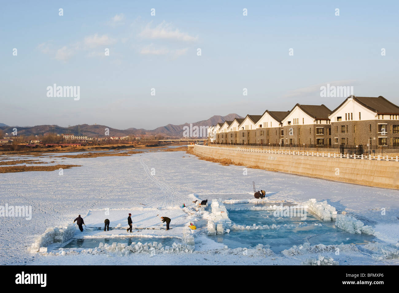 China, Hebei Province, Chengde, ice blocks being taken out of a frozen river - Stock Image