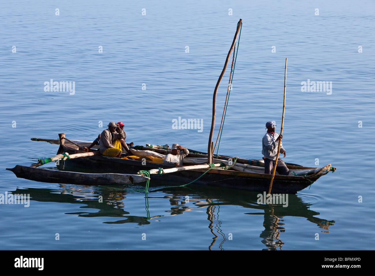 Tanzania, Zanzibar. In the morning, fishermen pole an outrigger canoe back to Zanzibars dhow harbour after fishing - Stock Image