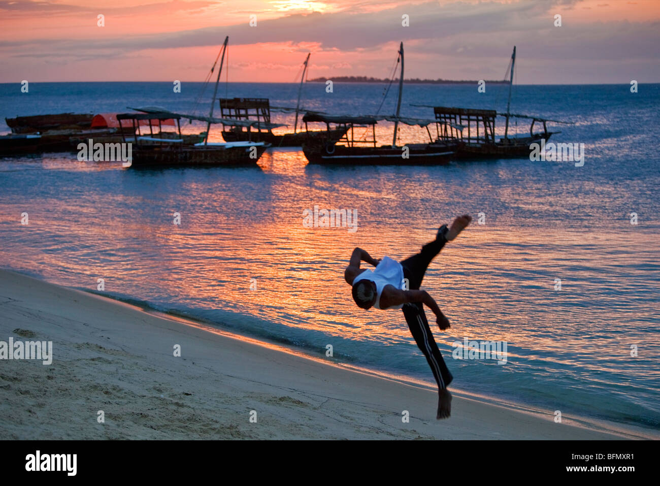 Tanzania, Zanzibar. At sunset, an acrobat practices somersaulting on the sandy beach west of Stone Town. Stock Photo