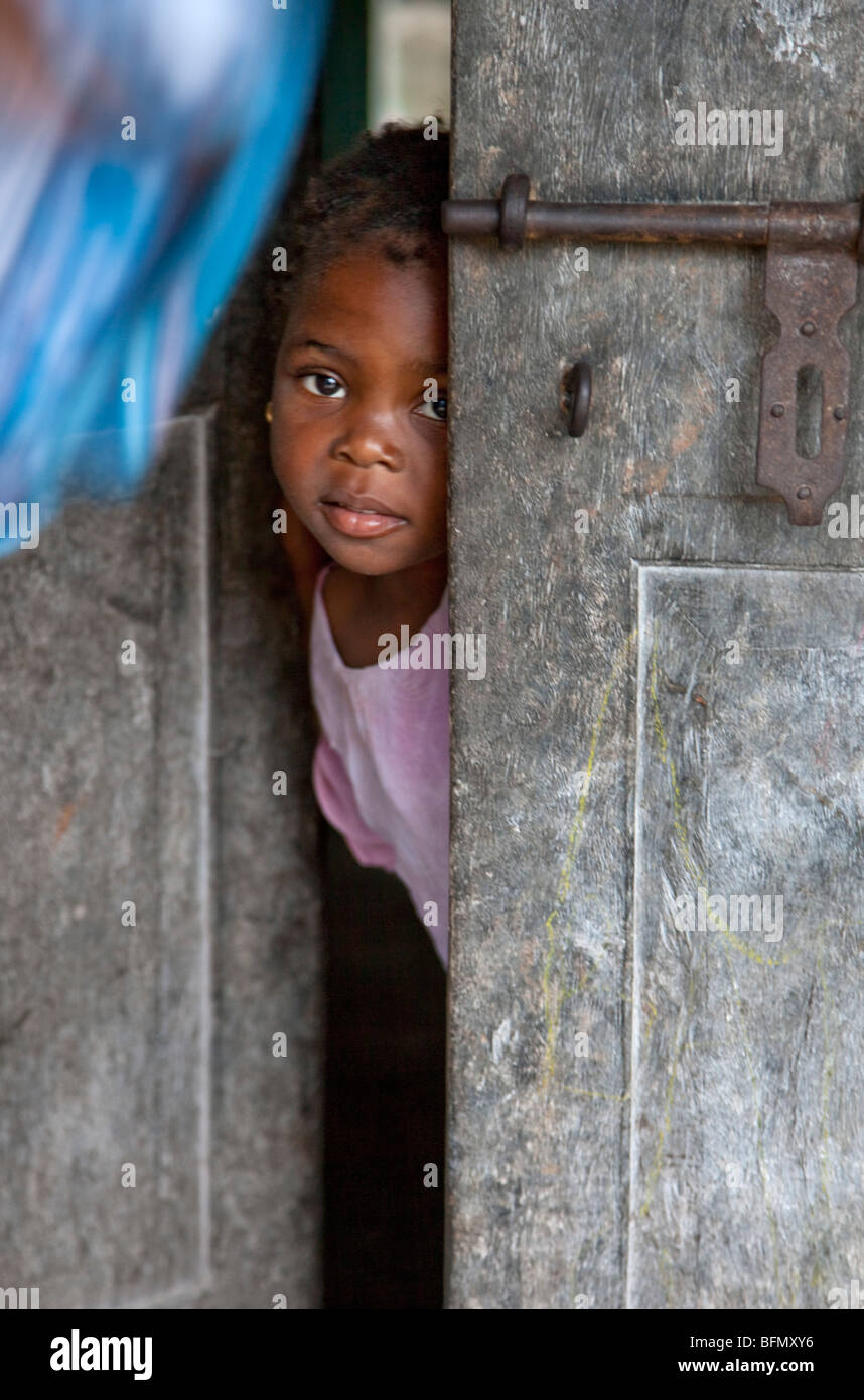 Tanzania, Zanzibar. A young girl peeps out from the front door of her home at Nungwi, the northern tip of Zanzibar - Stock Image
