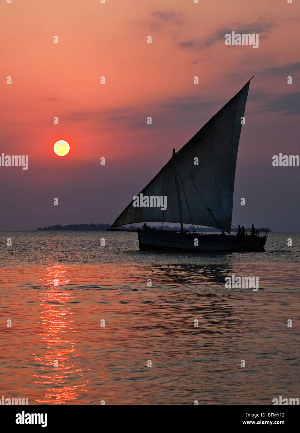 Tanzania, Zanzibar. A dhow sails back to Zanzibar harbour at sunset. - Stock Image
