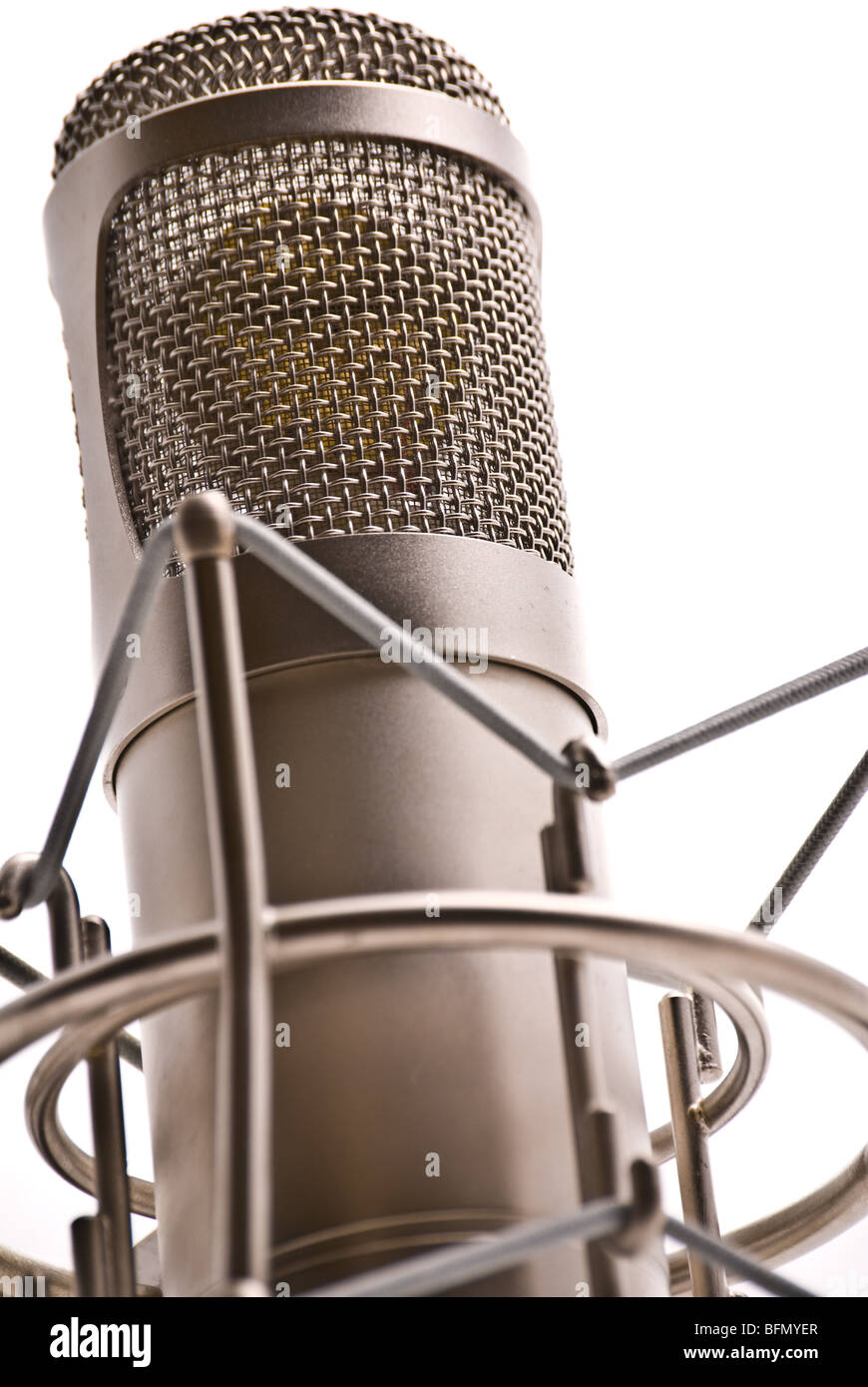 Close-up of a large diaphragm microphone in a shockmount against a white background - Stock Image