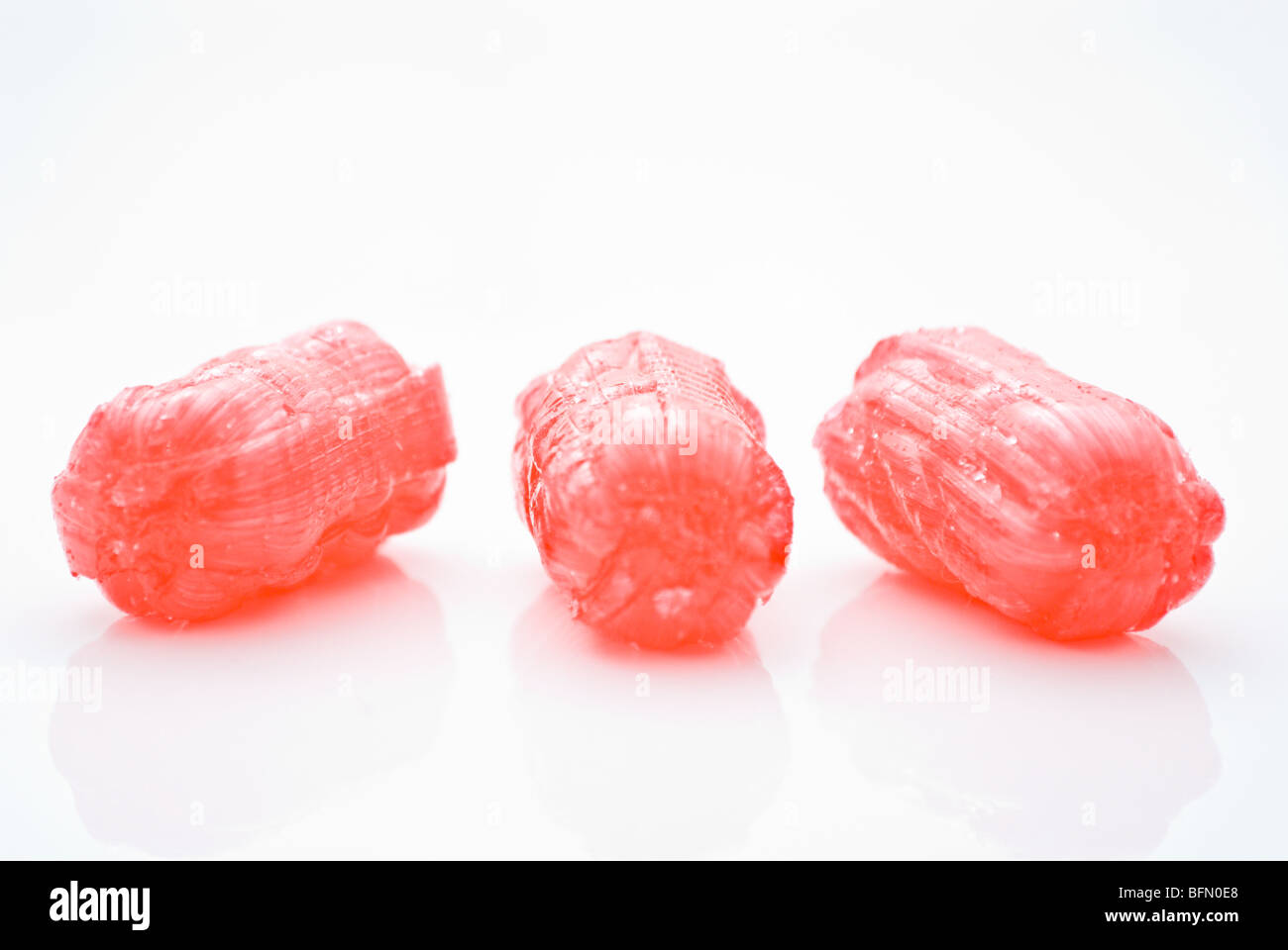 Red sweets on white background with reflection - Stock Image