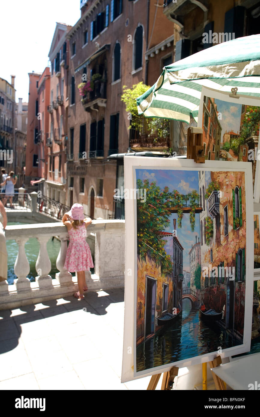 Venice, Italy. An artist's canvas depicting a Venetian canal and a young girl watches gondolas pass near St - Stock Image