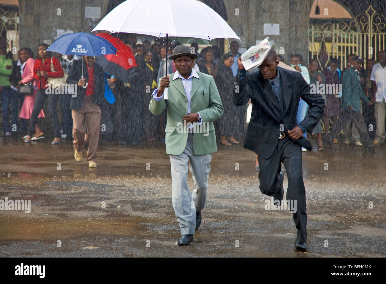 Kenya, Nairobi.  Commuters brave the rain at Nairobi Railway Station. - Stock Image