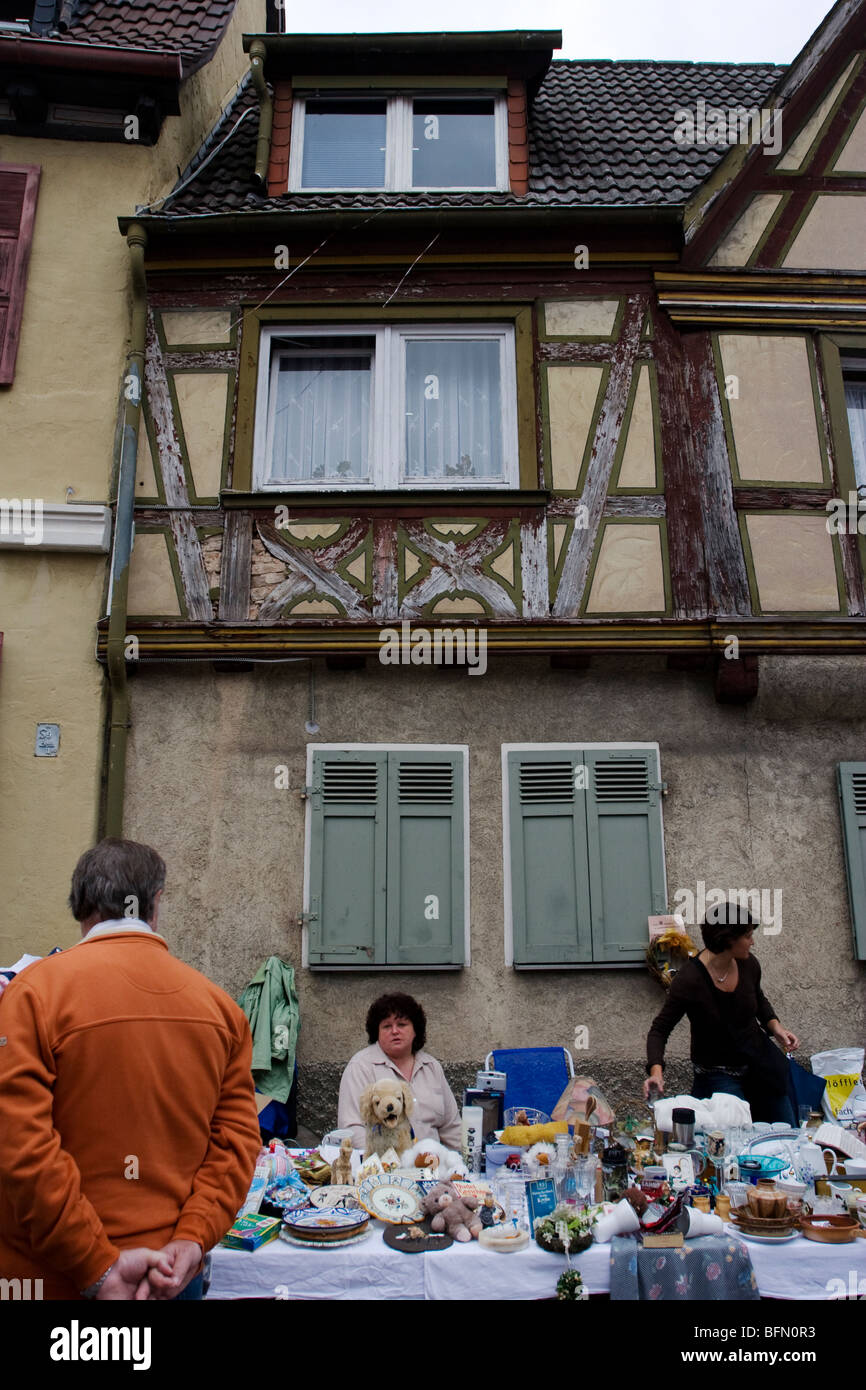 A flea market stall in front of a historical timber frame construction (Fachwerkbau) in Ladenburg, Germany - Stock Image