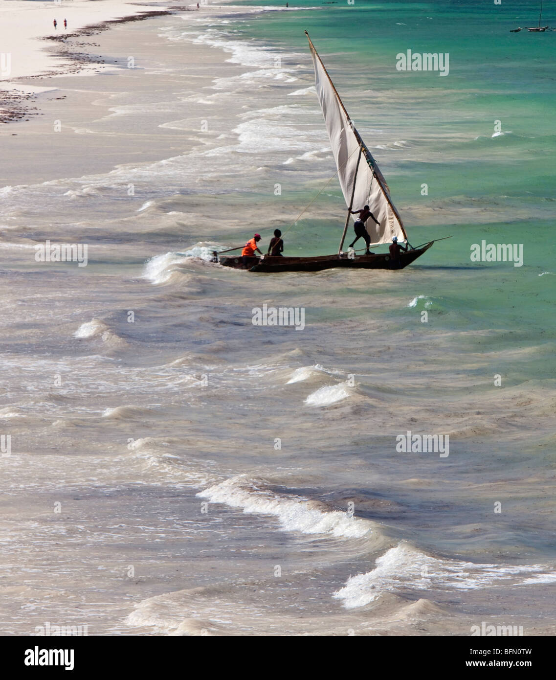 Kenya, Mombasa. An outrigger canoe sets sail from Diani Beach, a very popular tourist destination on Kenya  s south - Stock Image
