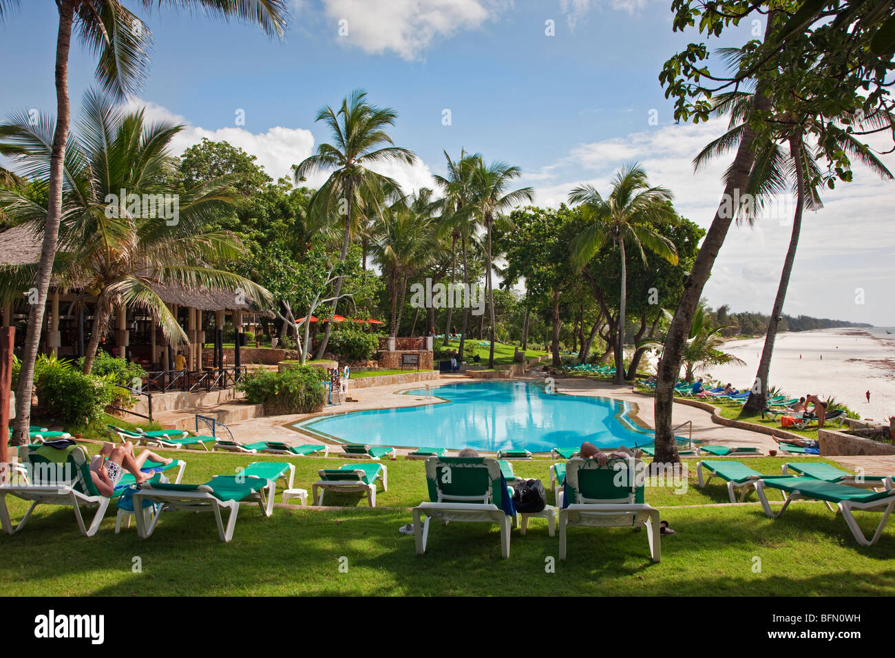 Kenya, Mombasa. The swimming pool of Baobab Resort with the white sands of Diani Beach in the background. - Stock Image