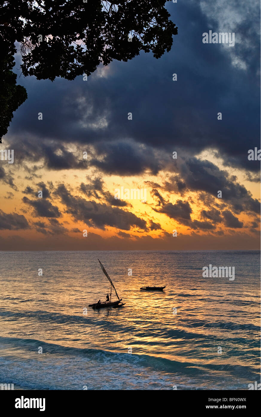 Kenya Mombassa. An outrigger canoe sets sail from Diani Beach at sunrise. - Stock Image