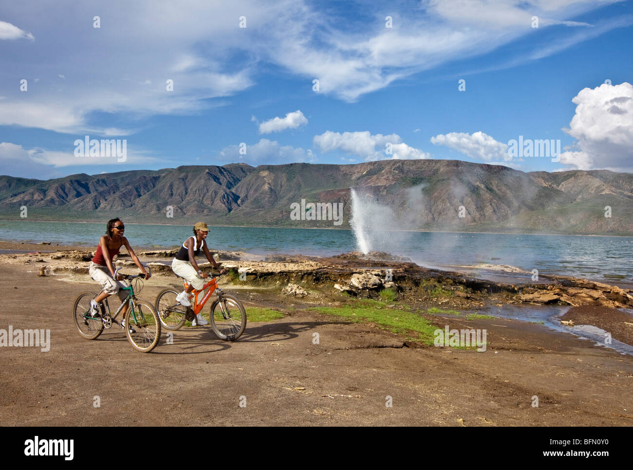 Kenya, Bogoria. Two girls cycle past the geysers and hot springs beside Lake Bogoria, an alkaline lake the Great - Stock Image