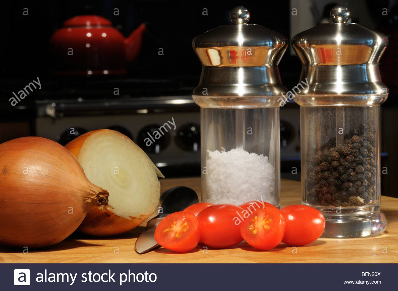 Close up image of onion and tomatoes with salt and pepper mills on a chopping board, Dorset, England, UK - Stock Image