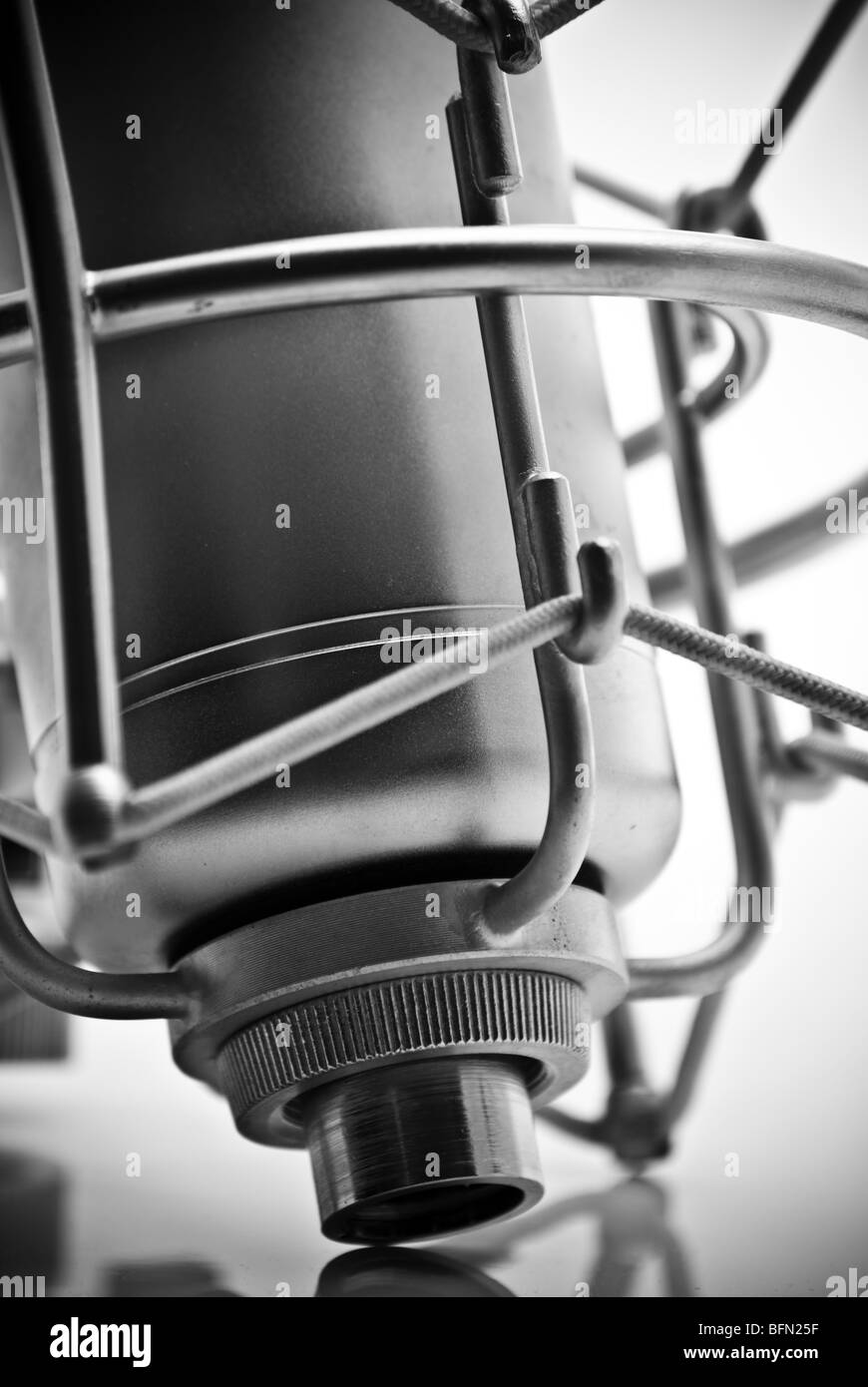 Black and white image of a microphone base and shockmount with some reflection - Stock Image